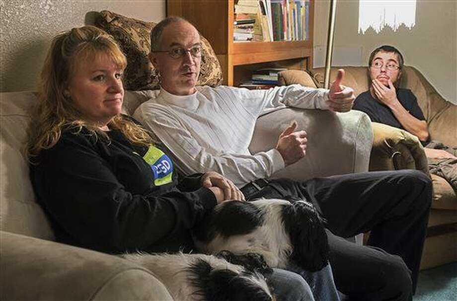 ADVANCE FOR WEEKEND EDITIONS - In this March 18, 2016 photo, Jina and Jerry Ezell talk about the confounding disease of their adopted son, Cody, sitting at right, at home in Longview, Wash. Ezell said he can lead a fairly normal life, despite living with a disease shared by only about 1,200 people nationally. (Bill Wagner/The Daily News via AP) MANDATORY CREDIT Photo: Bill Wagner