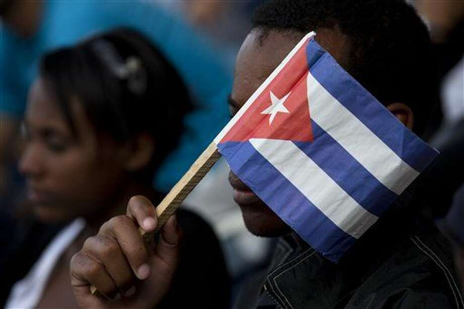 A Cuban fan uses a paper flag to shield his face from the sun during a baseball game between the Tampa Bay Rays and the Cuban national baseball team, in Havana, Cuba, Tuesday, March 22, 2016. Tampa Bay defeated the Cuban team 4-1 at a game attended by President Barack Obama and Cuba's President Raul Castro. (AP Photo/Rebecca Blackwell) Photo: Rebecca Blackwell