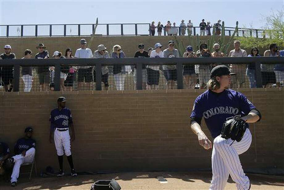 Fans watch as Colorado Rockies starting pitcher Jon Gray throws in the bullpen before a spring training baseball game between the Rockies and the Milwaukee Brewers in Scottsdale, Ariz., Tuesday, March 22, 2016. (AP Photo/Jeff Chiu) Photo: Jeff Chiu