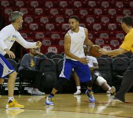 Golden State Warriors point guard Stephen Curry is double teamed by trainers as they practiced at Toyota Center, Wednesday, April 20, 2016, in Houston, as they prepared for Game 3 against the Houston Rockets in Round 1 of the playoffs. ( Karen Warren / Houston Chronicle )