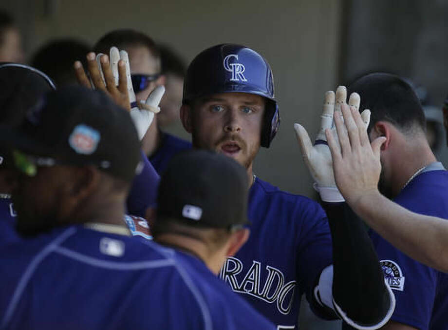 Colorado Rockies' Trevor Story celebrates with teammates after hitting a solo home run during the third inning of a spring training baseball game against the Texas Rangers, Saturday, March 26, 2016, in Scottsdale, Ariz. (AP Photo/Darron Cummings) Photo: Darron Cummings