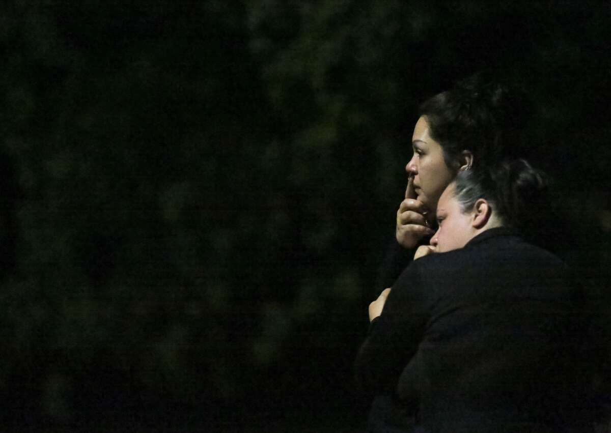 Two women watch as police talk to a group of people after crews pull a body from Sims Bayou on Wednesday.