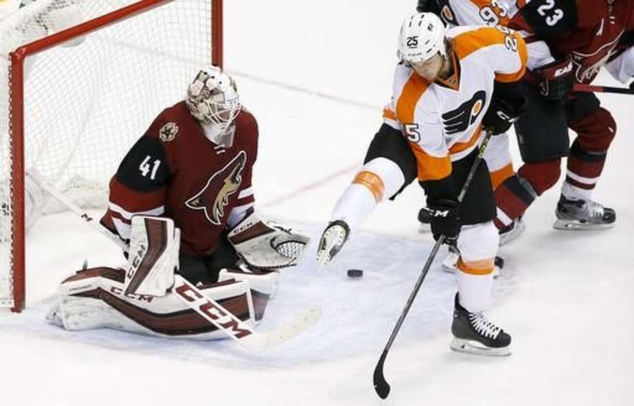 Philadelphia Flyers' Ryan White (25) tries to get out of the way of a shot as Arizona Coyotes' Mike Smith (41) moves in to make a save during the third period of an NHL hockey game Saturday, March 26, 2016, in Glendale, Ariz. The Coyotes defeated the Flyers 2-1. (AP Photo/Ross D. Franklin) Photo: Ross D. Franklin