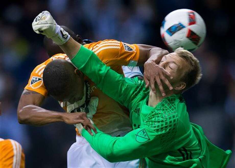 Houston Dynamo's Ricardo Clark, left, gets his hand on the face of teammate and goalkeeper Joe Willis as Willis tries to punch the ball away from Vancouver Whitecaps' Kekuta Manneh, rear, during the first half of an MLS soccer game in Vancouver, British Columbia, on Saturday, March 26, 2016. (Darryl Dyck/The Canadian Press via AP) Photo: DARRYL DYCK
