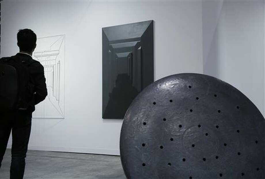 In this March 25, 2016 photo, a man looks at the artworks by Chinese artist Cai Lei at Art Basel in Hong Kong. Asia's biggest exhibition of modern and contemporary art brought together 239 galleries from 35 countries and territories in Hong Kong, which has emerged as the region's top art trading hub. (AP Photo/Kin Cheung) Photo: Kin Cheung