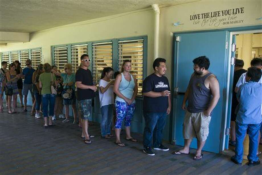 Voters line up outside a polling station set up at Kailua Intermediate School to register to vote in Hawaii's Democratic primary, Saturday, March 26, 2016, in Kailua, Hawaii. (AP Photo/Marco Garcia) Photo: Marco Garcia