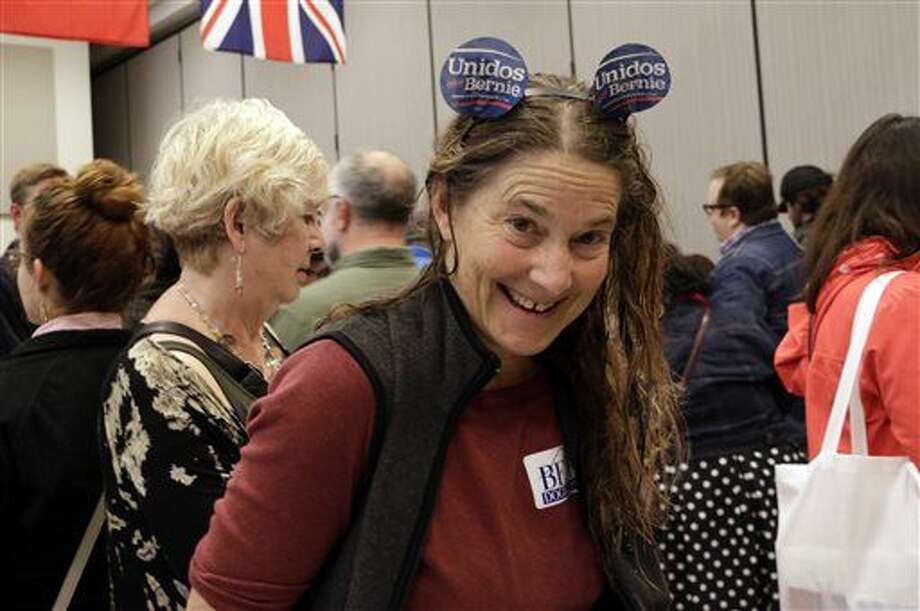 Laura Schleyer, a supporter of Bernie Sanders, mingles with other voters at a caucus site in Olympia, Wash., Saturday, March 26, 2016. Democrats caucused statewide in support of either Hillary Clinton or Bernie Sanders.. (AP Photo/Rachel La Corte) Photo: Rachel La Corte