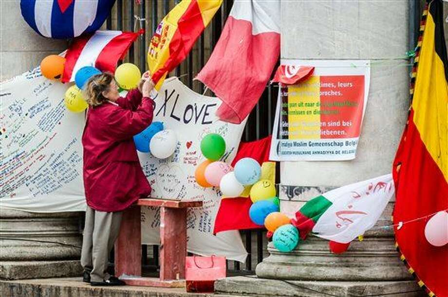 A woman attaches a message to a Spanish flag at a memorial site at the Place de la Bourse in Brussels, Sunday, March 27, 2016. In a sign of the tensions in the Belgian capital and the way security services are stretched across the country, Belgium's interior minister appealed to residents not to march Sunday in Brussels in solidarity with the victims. (AP Photo/Geert Vanden Wijngaert) Photo: Geert Vanden Wijngaert