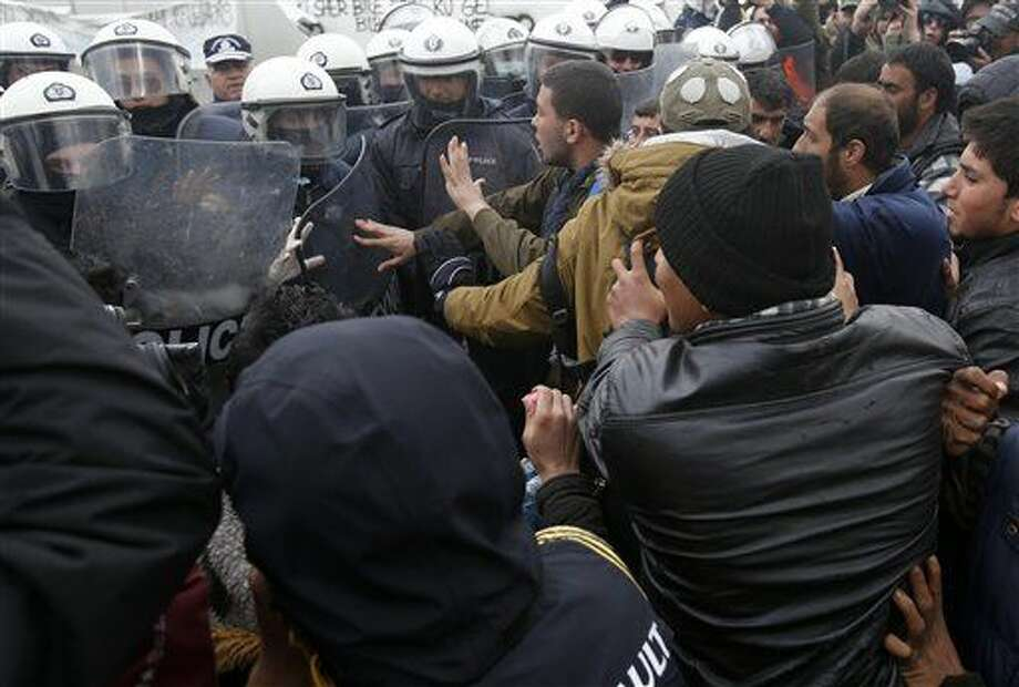 Migrants scuffle with police during a protest demanding the opening of the border between Greece and Macedonia in the northern Greek border station of Idomeni, Greece, Sunday, March 27, 2016. A split appears to have developed among the groups of migrants at the Idomeni border encampment, with Greek riot police who, so far, have used only their shields to protect the border. (AP Photo/Darko Vojinovic) Photo: Darko Vojinovic