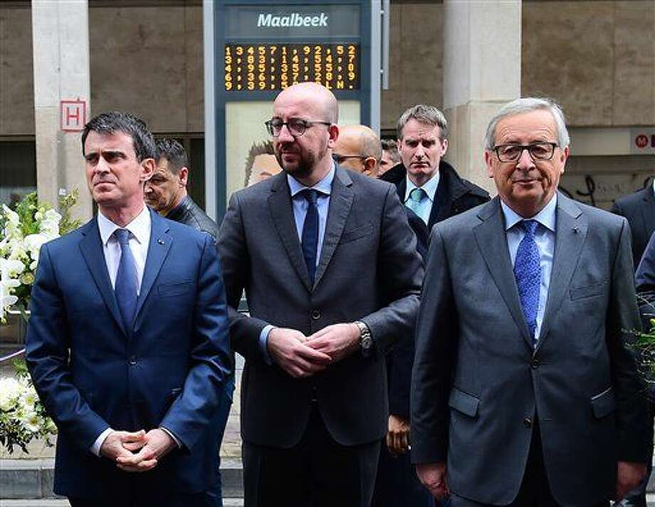From left, French Prime Minister Manuel Valls, Belgian Prime Minister Charles Michel and European Commission President Jean-Claude Juncker prepare to lay flowers at the Maelbeek metro station in Brussels on Wednesday, March 23, 2016. Belgian authorities were searching Wednesday for a top suspect in the country's deadliest attacks in decades, as the European Union's capital awoke under guard and with limited public transport after scores were killed and injured in bombings on the Brussels airport and a subway station. (Emmanuel Dunand, Pool Photo via AP) Photo: Emmanuel Dunand