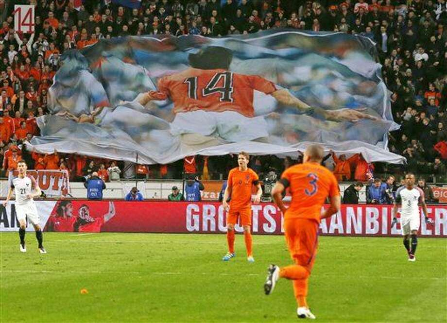 A banner with a picture of deceased legendary soccer player Johan Cruyff who played with number 14, is seen after players of the Dutch and French soccer squads observed a minute of silence in the 14th minute of the game during the international friendly soccer match between The Netherlands and France at the ArenA stadium in Amsterdam, Netherlands, Friday, March 25, 2016. (AP Photo/Peter Dejong) Photo: Peter Dejong