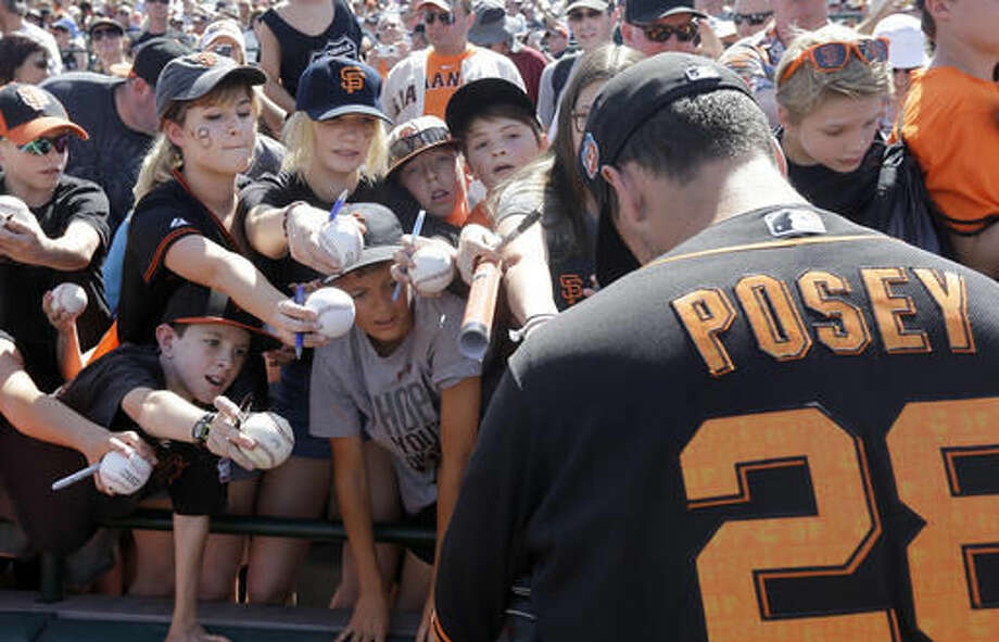 San Francisco Giants catcher Buster Posey gives autographs to fans before a spring training baseball game against the Oakland Athletics in Scottsdale, Ariz., Monday, March 21, 2016. (AP Photo/Jeff Chiu) Photo: Jeff Chiu