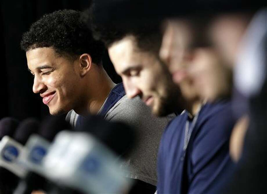 Virginia forward Isaiah Wilkins, left, smiles as he listens to head coach Tony Bennett speak during a news conference, Saturday, March 26, 2016, in Chicago. Virginia plays against Syracuse in a regional final game in the men's NCAA Tournament on Sunday. (AP Photo/Nam Y. Huh) Photo: Nam Y. Huh