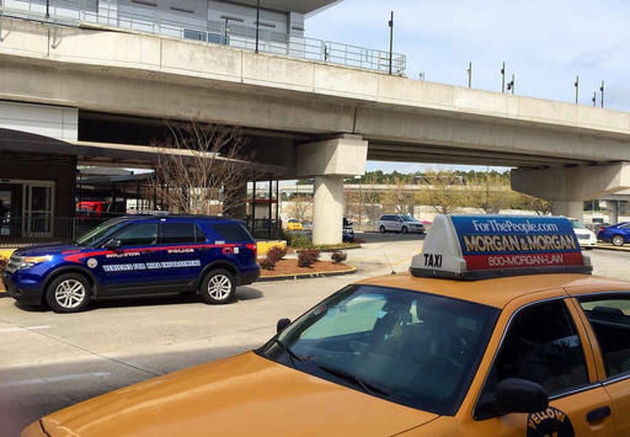 In this March 25, 2016 photo, an Atlanta Police Rides-For-Hire Enforcement vehicle sits amid taxi cabs outside the departures area of the domestic terminal at Hartsfield-Jackson Atlanta International Airport. A battle over background checks for Uber drivers at the world's busiest airport comes as cities like Los Angeles and Austin, Texas, consider more thorough screenings to prevent criminals from getting behind the wheel. Uber has objected to the use of fingerprints to check criminal records of its drivers, saying its own record checks are sufficient. (AP Photo/Jeff Martin) Photo: Jeff Martin