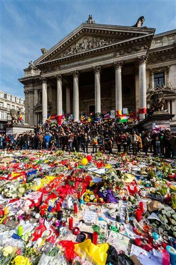 People gather at floral tributes at a memorial site at the Place de la Bourse in Brussels, Saturday, March 26, 2016. Brussels airport officials say flights won't resume before Tuesday as they assess the damage caused by twin explosions in the terminal earlier this week. (AP Photo/Geert Vanden Wijngaert) Photo: Geert Vanden Wijngaert