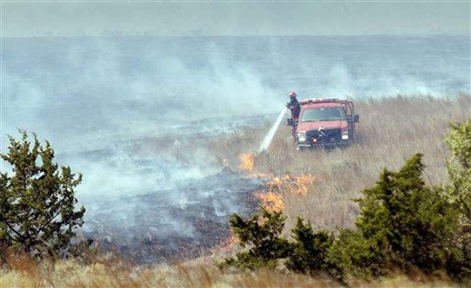 Un bombero combate las llamas que destruyen el pasto a unos 24 kilómetros (15 millas) al suroeste de Medicine Lodge, Kansas, el jueves 24 de marzo de 2016. Los bomberos que intentan apagar el incendio más grande en la historia de Kansas recibieron el sábado 26 de marzo la asistencia de helicópteros militares, y quizá consigan después la de una lluvia o una nevada, según los pronósticos meteorológicos. (Mike Hutmacher/The Wichita Eagle vía AP) ESTA FOTOGRAFÍA NO DEBE SER UTILIZADA POR MEDIOS LOCALES.
