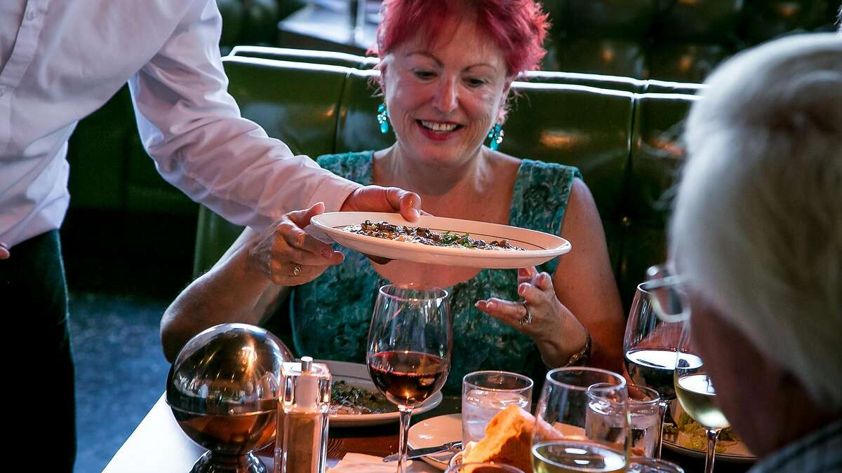 A server brings food to a table at Original Joes of Westlake in Daly City, Calif., on April 20th, 2016.