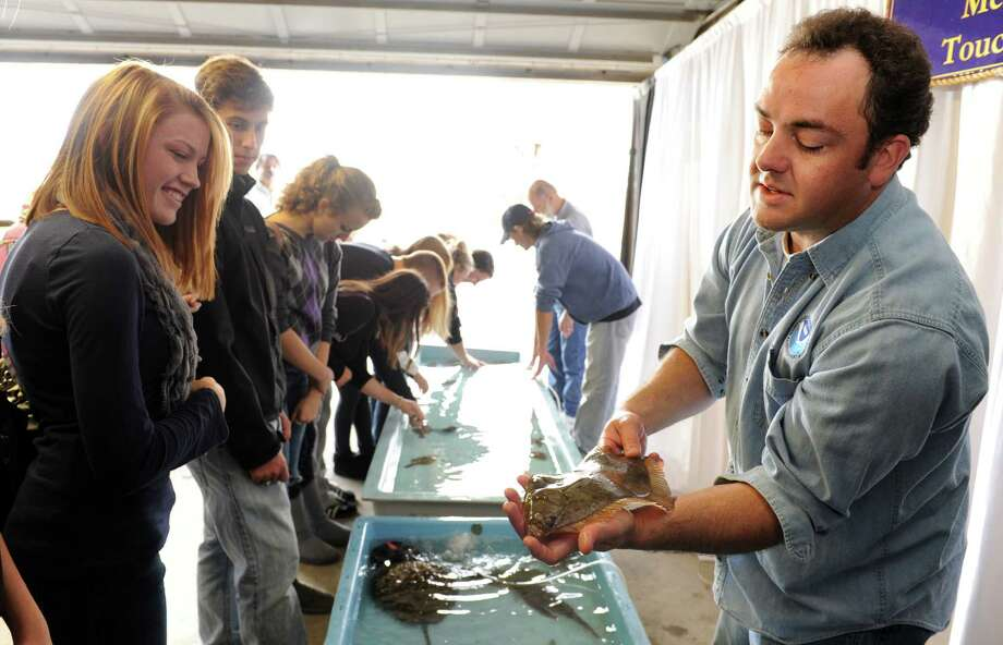 NOAA researcher and lab tech, David Veilleux, holds out a flounder for Jonathan Law seniors to examine Friday Oct. 15, 2010 during an open house at the National Oceanic and Atmospheric Agency lab in Milford. Photo: Autumn Driscoll / ST / Connecticut Post