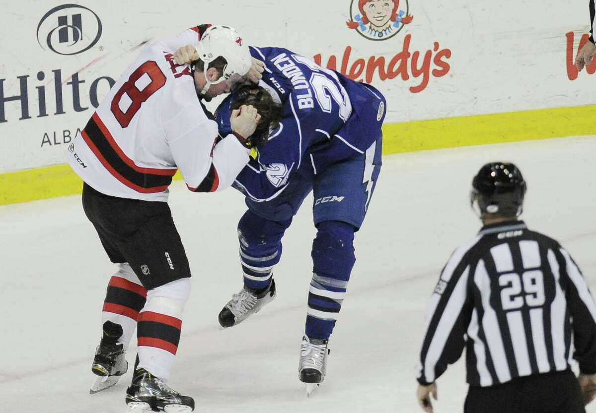 Albany Devils' Dan Kelly (8) and Syracuse Crunch's Mike Blunden (21) fight during the first period of an AHL hockey game in Albany, N.Y., Friday, Jan. 8, 2016. (Hans Pennink / Special to the Times Union) ORG XMIT: HP106 ORG XMIT: MER2016010820531716