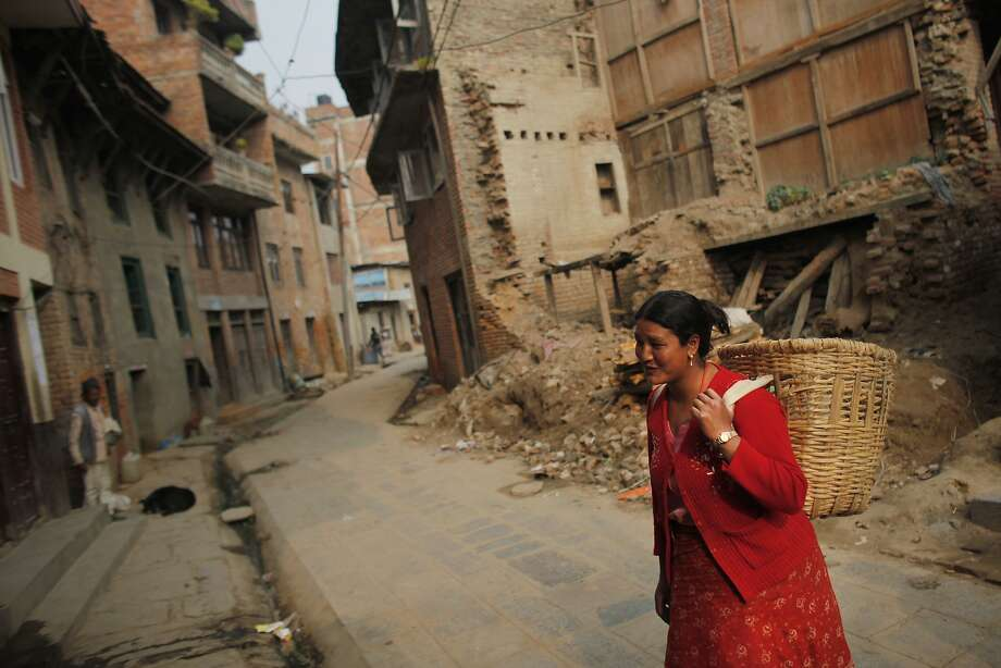 A woman walks past houses damaged in last year's 7.8-magntitude earthquake in the central village of Khokana. The quake devastated countless towns and villages. Photo: Niranjan Shrestha, Associated Press
