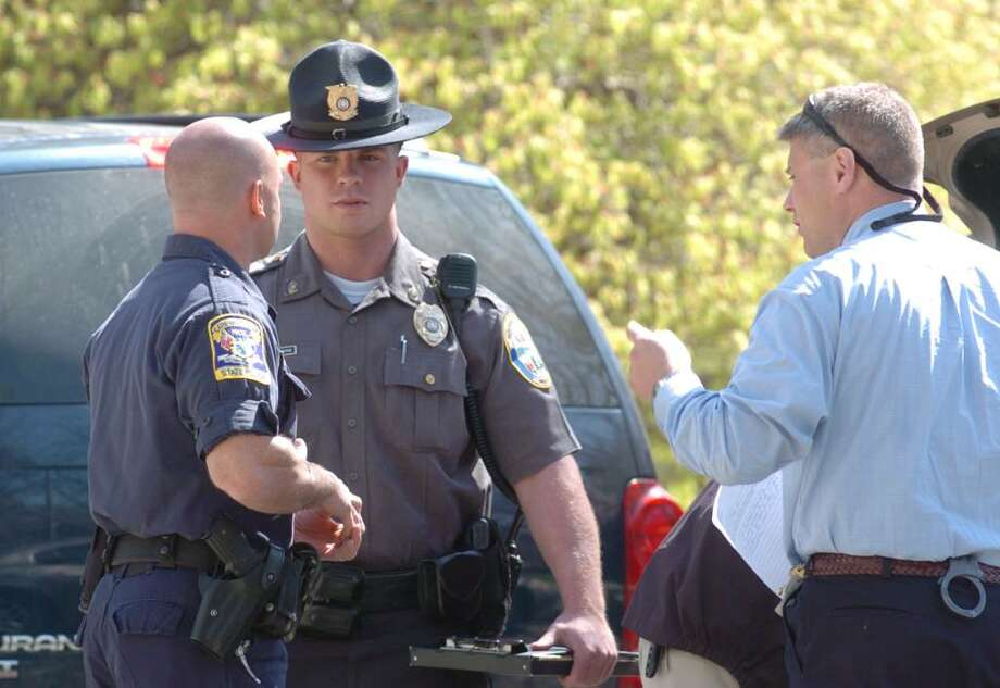 From right, Detective Jason Frank and Officer Bart Lorancaitis of Newtown Police Department chat with Connecticut State Police while on the crime scene at 89 Poverty Hollow Road in Newtown, April 15, 2010.  Earlier today, Connecticut Major Crime Squad and state detectives are assisting Newtown police with an investigation into what is believed to be human remains found under the basement subfloor of a barn located at 89 Poverty Hollow Road early Wednesday afternoon. The bones were found by the homeowners who were removing flooring. Photo: Chris Ware / The News-Times