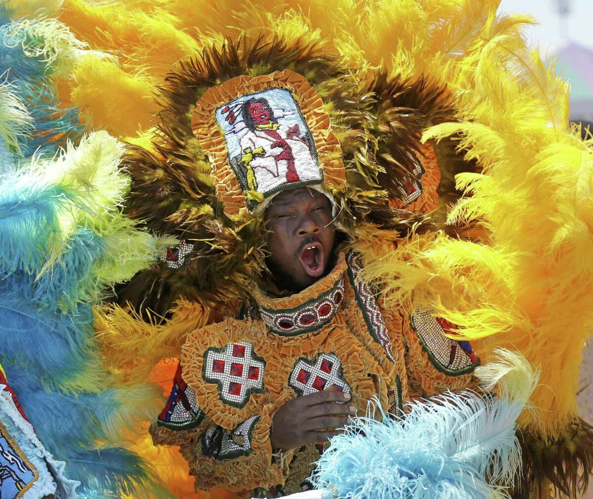 FILE - In this file photo, Members of the New Orleans Mardi Gras Indian Rhythm Section, with the Algiers Warriors and Golden Comanche Mardi Gras Indians, march in a second line parade at the New Orleans Jazz and Heritage Festival in New Orleans, Friday, May 1, 2015. The 47th annual festival features top artists covering many genres of music from jazz to rock to Zydeco to rap to pop to R&B and gospel. The gates to the Fair Grounds Race Track, where the festival is held, open at 11 a.m. The music on 11 stages starts shortly thereafter. (AP Photo/Gerald Herbert, File) ORG XMIT: LAGH207