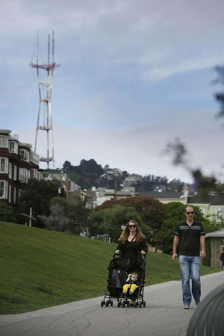 Kirsty Perrett (l to r), pushes Zephina Robertson, 7 months, in a stroller as Graham Robertson walks alongside while out for a walk  at Dolores Park  on Thursday, April 21, 2016 in San Francisco, California. Photo: Lea Suzuki, The Chronicle
