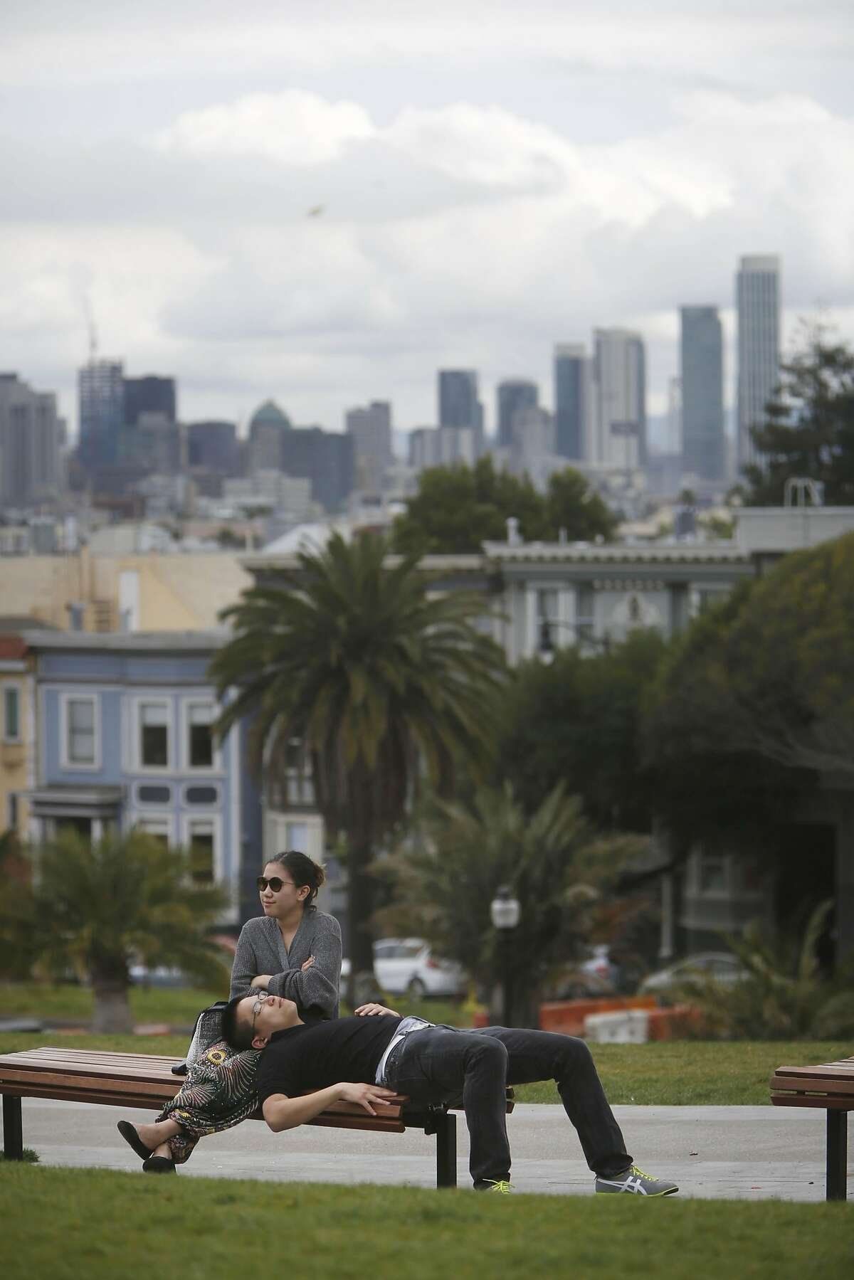 Emiz Zhong (l to r) and Elvin He, both of New York, relax in Dolores Park after arriving from Los Angeles at 5 A.M. while on vacation as they visit at Dolores Park on Thursday, April 21, 2016 in San Francisco, California.