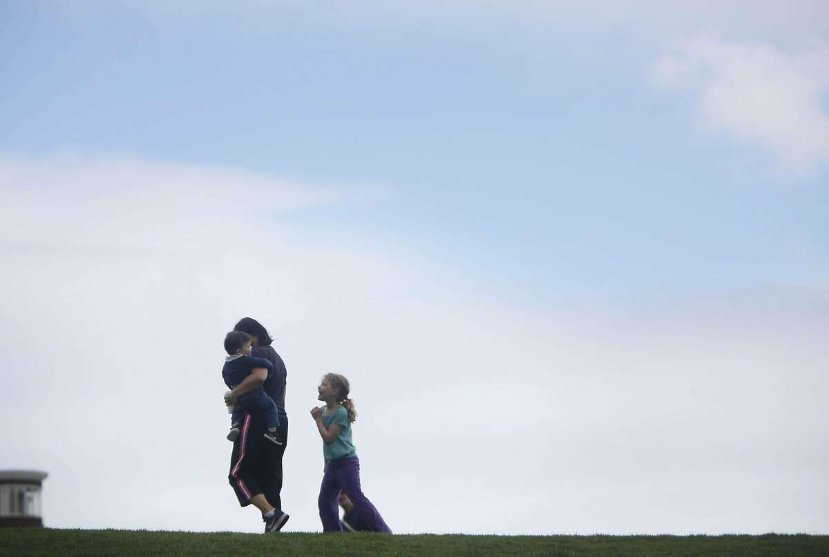 Rachel Bauer (center) holds her son Ari Bauer (left), 15 months, both of San Francisco, as her niece Eliana Zimbauer (right), 7, visiting from Madison. Wisconsin, walk through Dolores Park as they sky begins to show through clouds on Thursday, April 21, 2016 in San Francisco, California.