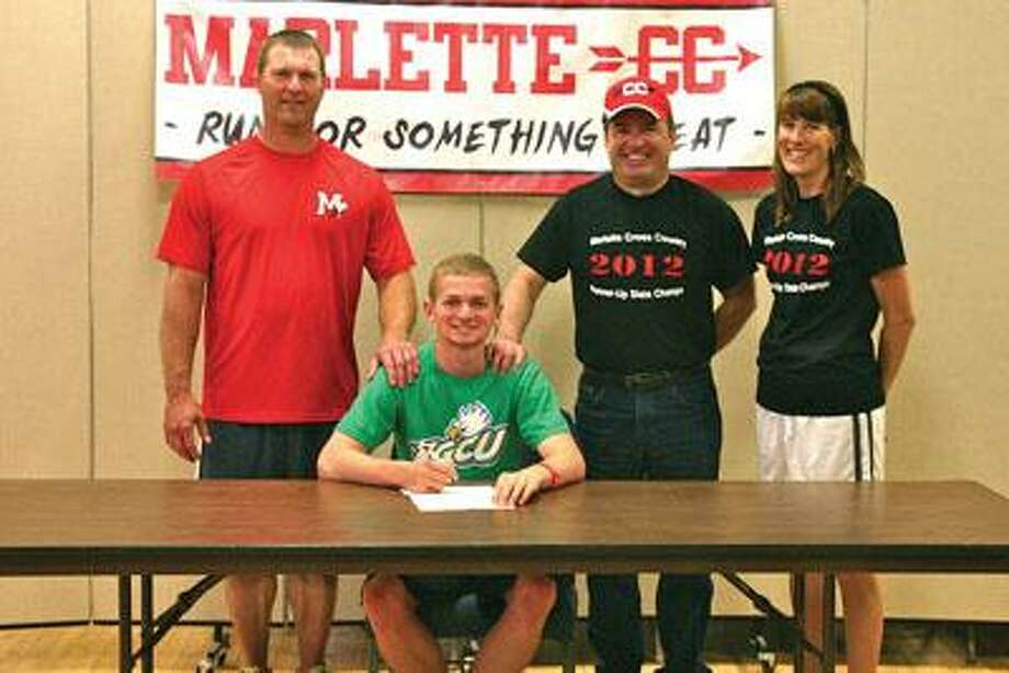 Marlette senior Mathew Titus signs his National Letter of Intent to run at Florida Gulf Coast University as he is flanked by high school track coach Chris Storm, left, and his father and cross country coach Chris Titus and assistant cross country coach Celina Bowman.