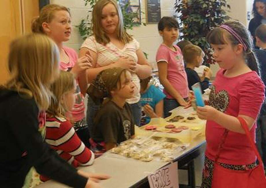 Traci L. Weisenbach/For the TribuneAlayna Wanless (right) checks out the baked goods at one of the tables during USA Elementary's Entrepreneurship Week, during which students sold various items to raise money for the Great Start Tuscola Imagination Library. Students raised about $200 for the program that sends age-appropriate books to preschool-aged children each month. The program is operated on donations only.