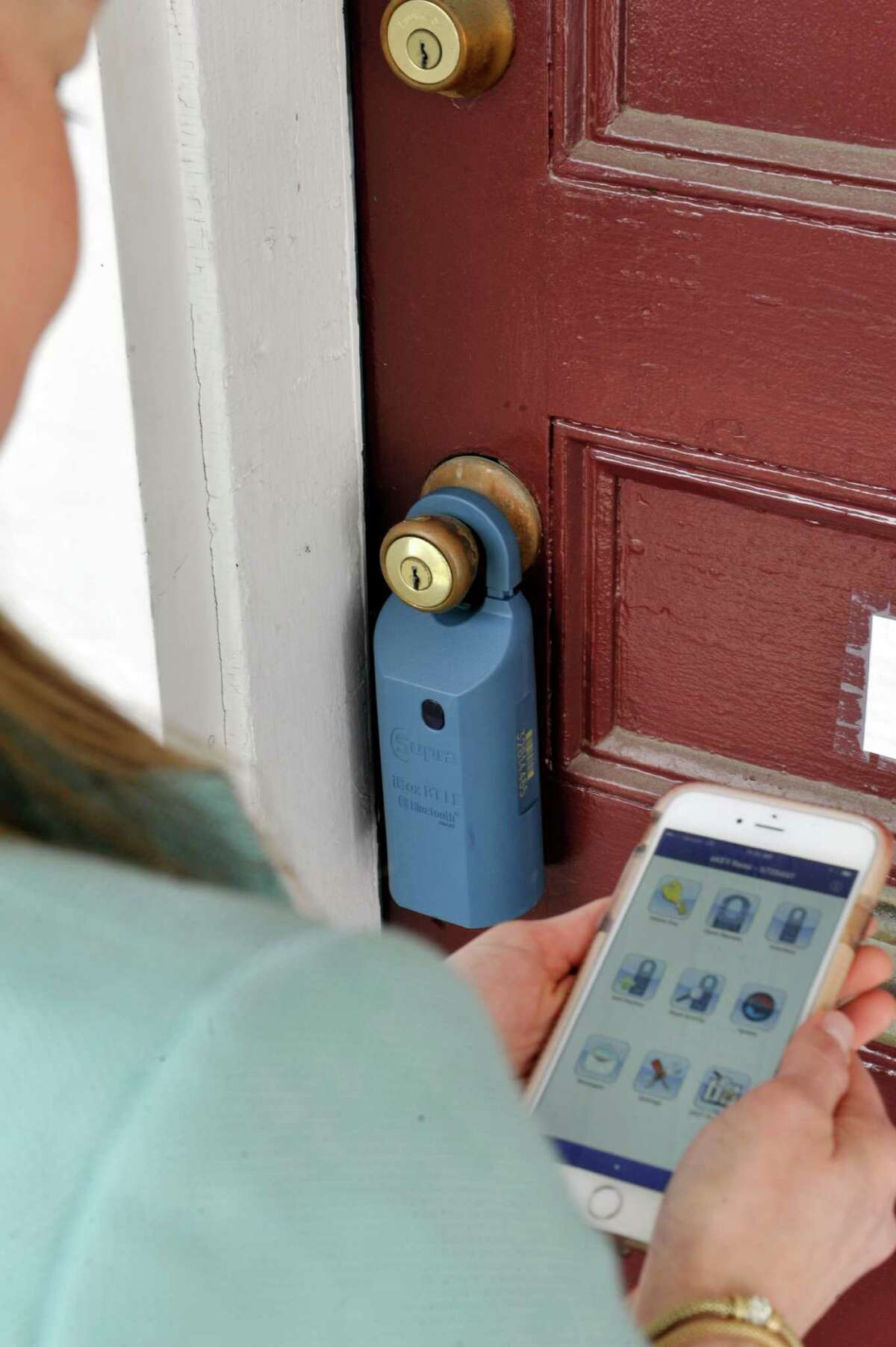 Judi Gabler, a real estate agent with Realty USA demonstrates how the iBox, a secure key holder, works on Tuesday, April 19, 2016, in Delmar, N.Y. (Paul Buckowski / Times Union)