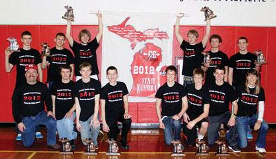 This Cross Country team will forever be in Marlette history. Hoisting their banner and displaying their finalist trophies are team members (back row left to right): junior Hayden Harneck, senior Daniel Groat, senior Matt Chappel, senior Nicholas Shaver, senior Mat Titus and senior Casey Johnson. Kneeling row: Head Coach Chris Titus, junior Alex Herman, sophomore Andrew Clark, freshman Eric Poth, senior Andy Bowman, senior Jacob Bowman, junior Eli Poth and assistant Coach Celina Bowman.