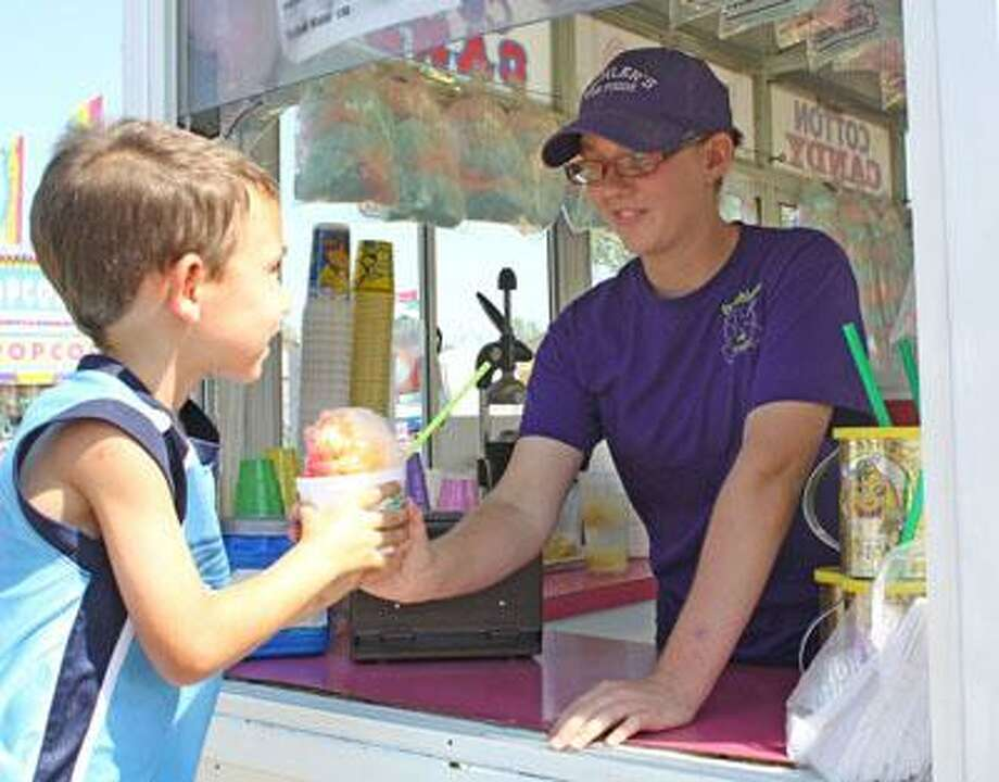 Rich Harp/For the Tribune Rachel Bechler hands an order of shaved ice to a Caseville boy while working one of her family's concession wagons at the Huron Community Fair.