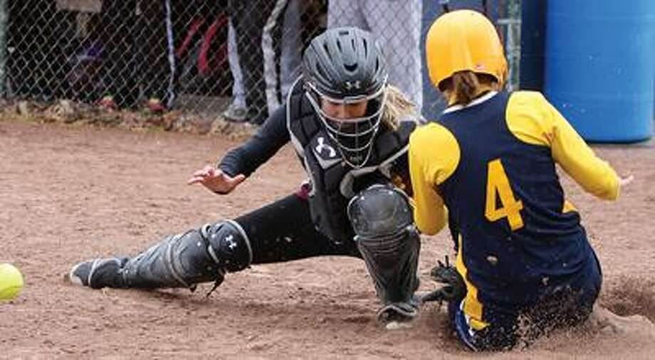 North Huron's Kim Koroleski (4) is safe at home as the ball gets away from Deckerville catcher Jenna Genoff during Game 1 on Thursday in Port Austin.For more sports photos, go to www.michigansthumb.com and click on the sports gallery.