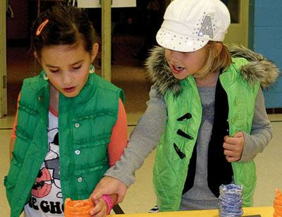 In this picture, first grader Callie Engler (left) and her big sister, third grader Alayna Engler, look at a table filled with clay pots in red, orange, blue and black.
