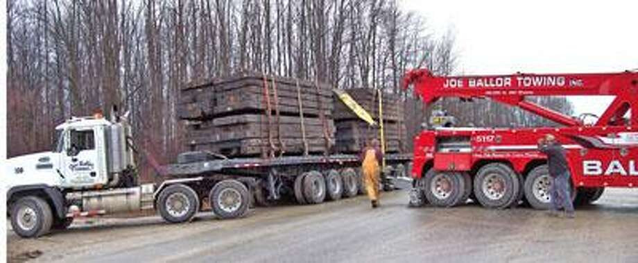 Workers try to straighten timber on this semi.