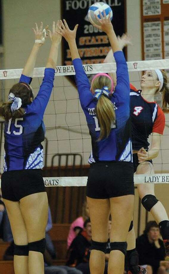 USA's Erica Treiber (4) attempts a kill over a pair of Hemlock players.