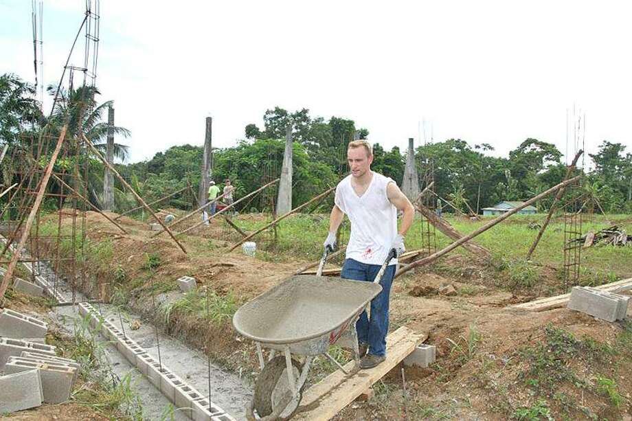 Missionary and Youth Pastor Ryan Badgerow of Pigeon works on pouring cement for the foundation of a multi-purpose building in Punta Gorda, Belize