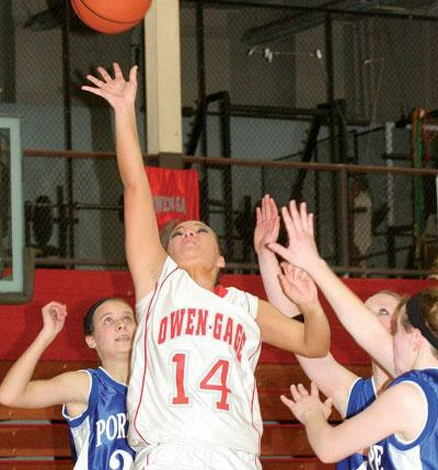 Owen-Gage's Lacie Prich (14) splits a trio of Port Hope defenders, including Taylor Reinke and Otyllia Abraham during the second quarter of the Bulldogs' 44-43 overtime victory on Monday night in Owendale.For more sports photos, go to www.michigansthumb.com and click on the sports gallery.