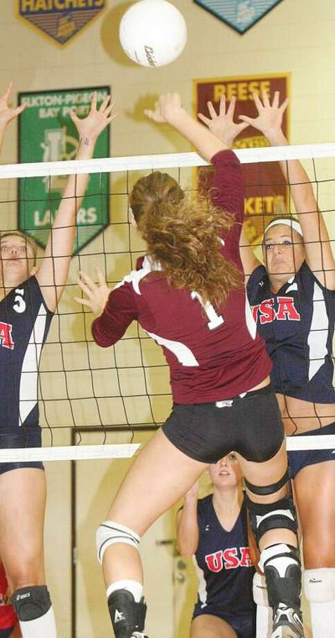 Cass City's Stephanie Leeson (1) goes for a kill against USA defenders Miranda Fuerst (5) and Ashlyn VanHoost (2) during Game 1 on Thursday.