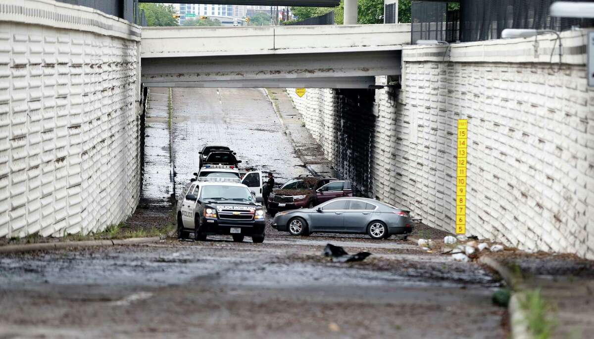 Police investigate the scene Monday at Loop 610 North near Westpark Drive, where at least one driver died after getting trapped in floodwaters. Such accidents could be prevented by technology.