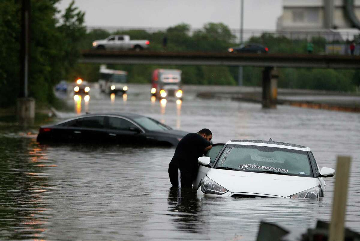 Alex Sanchez looks through the window of his stranded car at the North Main Street exit off of North I-45, as White Oak Bayou comes out of it's banks, flooding the freeway, Monday, April 18, 2016, in Houston. ( Karen Warren / Houston Chronicle )
