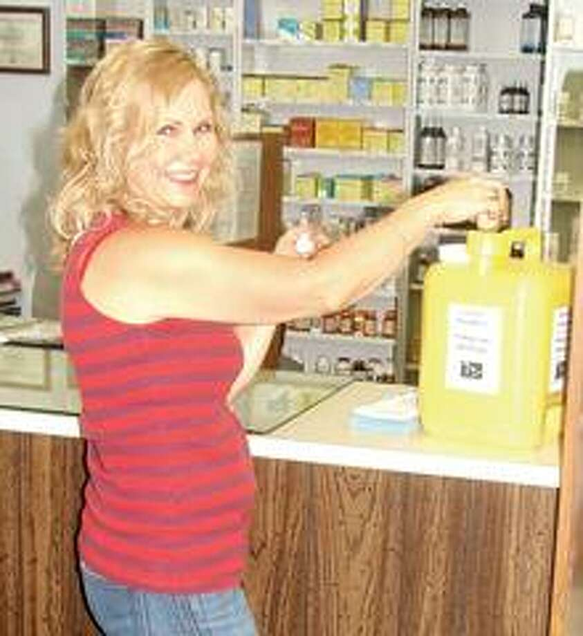 Pharmacy Technician Barb McMillan disposes of some unwanted medications through the Yellow Jug program at Mainstreet Pharmacy in Marlette.