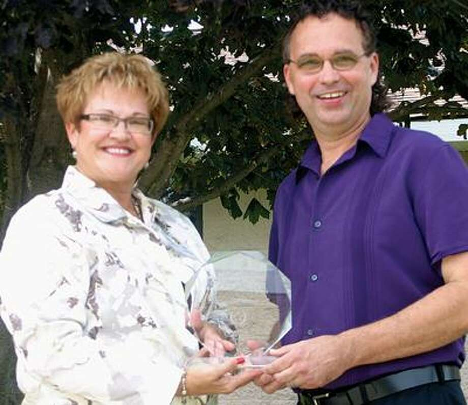 Kay Peruski, Courtney Manor administrator, gives an award to Bad Axe musician Johnny Prill. Prill recently was chosen as the Volunteer of the Year by the Healthcare Association of Michigan. Peruski nominated him. Prill has been volunteering at Courtney Manor for 25 years.Traci L. Weisenbach/Huron Daily Tribune