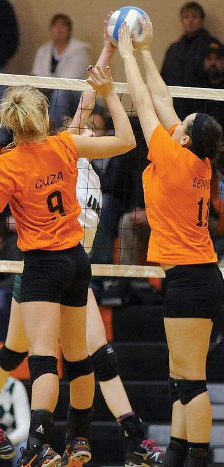 Ubly teammates Michela Guza (9) and Janelle Leppek (11) go for a block on EPBP's Brittany Hatfield.
