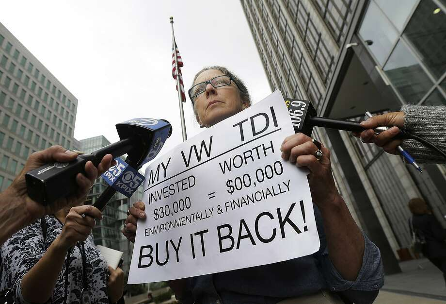 Joyce Ertel Hulbert, owner of a 2015 Volkswagen Golf TDI, holds a sign while interviewed outside of the Phillip Burton Federal Building in San Francisco, Thursday, April 21, 2016. An agreement will give consumers who bought nearly 600,000 Volkswagen vehicles rigged to cheat on emissions tests the option of having the automaker buy back the cars or fix them, a judge said Thursday. Photo: Jeff Chiu, Associated Press