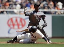 Arizona Diamondbacks second baseman Jean Segura, top, turns a double play over San Francisco Giants' Hunter Pence on a ground ball from Brandon Belt during the third inning of a baseball game, Thursday, April 21, 2016, in San Francisco. (AP Photo/Marcio Jose Sanchez)