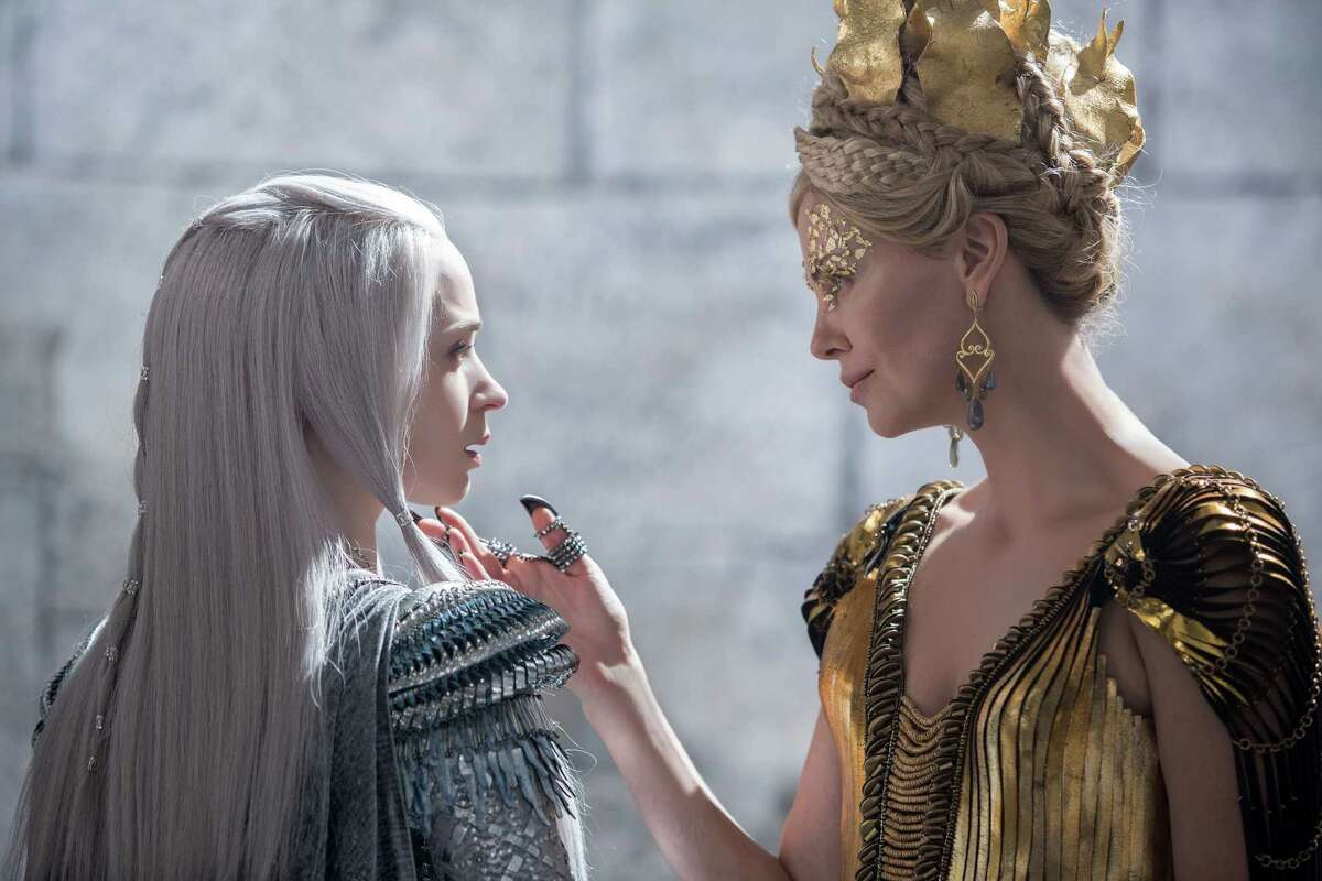 """In this image released by Universal Pictures, Emily Blunt, left and Charlize Theron appear in a scene from """"Huntsman: Winter's War."""" (Giles Keyte/Universal Pictures via AP)"""