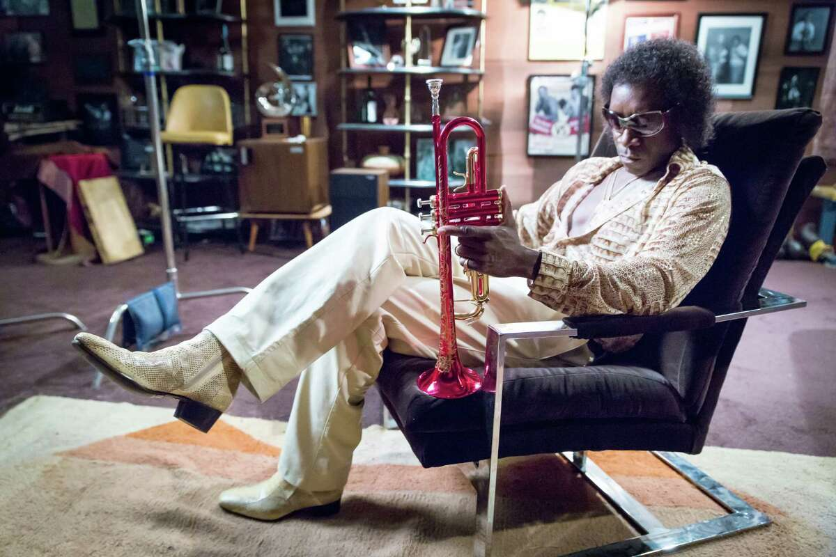 """As Miles Davis in """"Miles Ahead,"""" Don Cheadle goes beyond capturing the legend's hushed, raspy voice, precise trumpet fingering, violent temper and showoff wardrobe."""